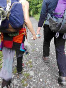 Zwei Wanderinnen im Gehen - zwischen ihnen sieht man, wie jede eine Hand am zusammengeklappten Langstock hat.