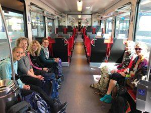 Die neun Wanderteilnehmerinnen sitzen sich im Zug im Fahrradabteil gegenüber.