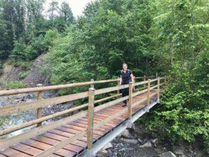 Eine Pilgerin überquert eine Holzbrücke.