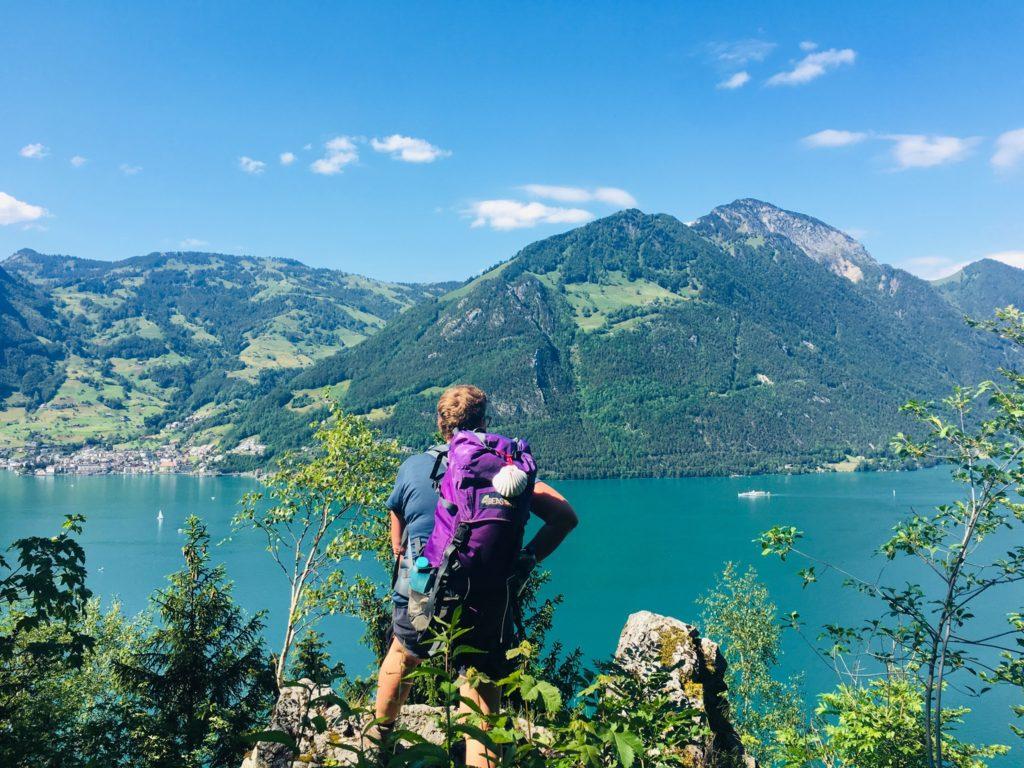 Auf einem Felsplateau über Baumwipfeln steht eine Pilgerin und blickt auf einen tiefblauen See, über dem graugrün melierte Berge aufragen, darüber blauer Himmel mit Schäfchenwolken.
