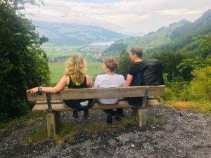 Drei Pilgerinnen sitzen auf einer Holzbank und blicken in die Ferne.