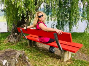 Knallrote Bank auf grüner Wiese unter einer Weide am Fluss. Darauf sitzt eine blonde Frau und strahlt den Betrachter an.
