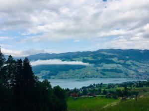 Ausblick auf den Sarner See mit Bergen darum und tiefhängenden Wolken.