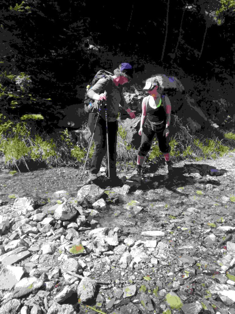 Zwei Pilgerinnen überqueren ein steiniges Flussbett - eine Sehende hilft einer Sehbehinderten dabei.