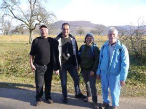 Vier Wanderer stehen beisammen. Im Hintergrund sieht man den Albtrauf und davor eine weitläufige Wiese mit vereinzelt Bäumen darauf.