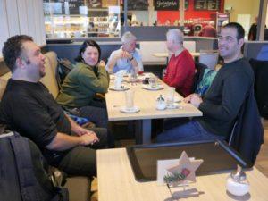 Fünf Personen sitzen in einem Café an einem Tisch. Zwei unterhalten sich, die anderen blicken in die Kamera.