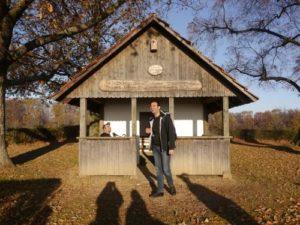 Umgeben von Bäumen, deren Äste man rechts und links am Bildrand erkennen kann steht in der Mitte des Fotos eine Wanderschutzhütte. Ein Mann steht vor der Hütte und lacht.
