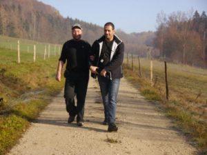 Zwei Männer wandern auf einem Feldweg. Ein Mann hat sich dabei bei dem anderen Mann am Arm eingehakt.
