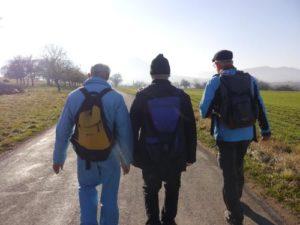 Auf diesem Foto sieht man drei Männer von hinten. Sie haben alle einen Rucksack auf dem Rücken und gehen auf einer geteerten Straße.