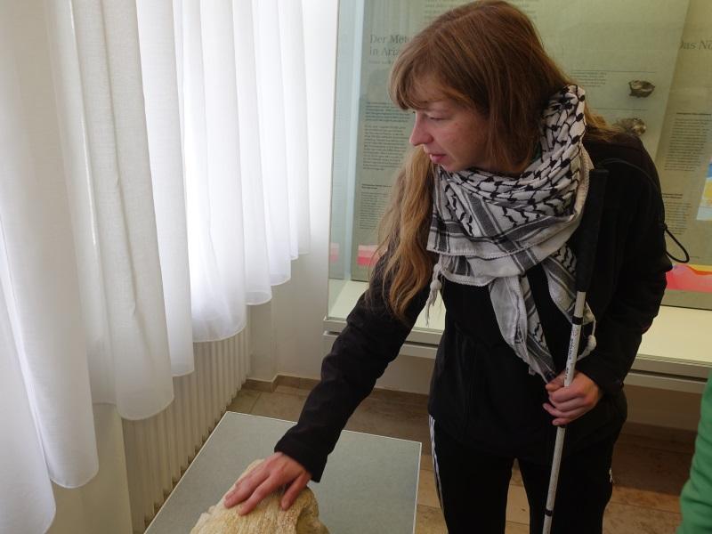 Blinde Frau erfühlt steinernes Exponat