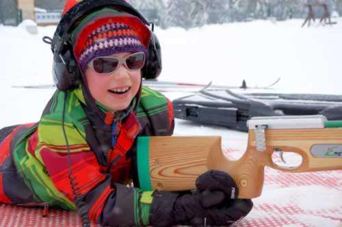 lachendes seebehindertes Mädchen am Biathlon-Schießstand