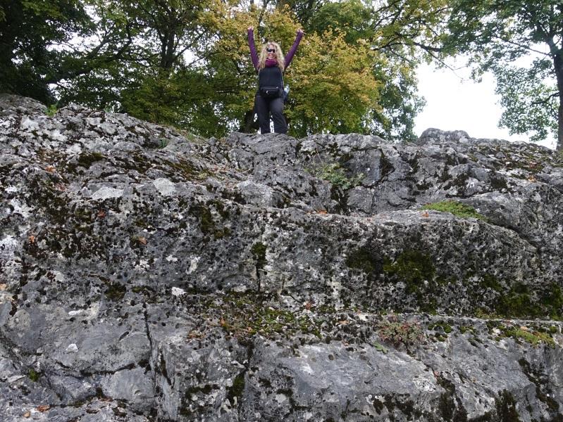 Eine Wanderin ist auf einen großen Felsen mit Bohrmuschellöschern geklettert.