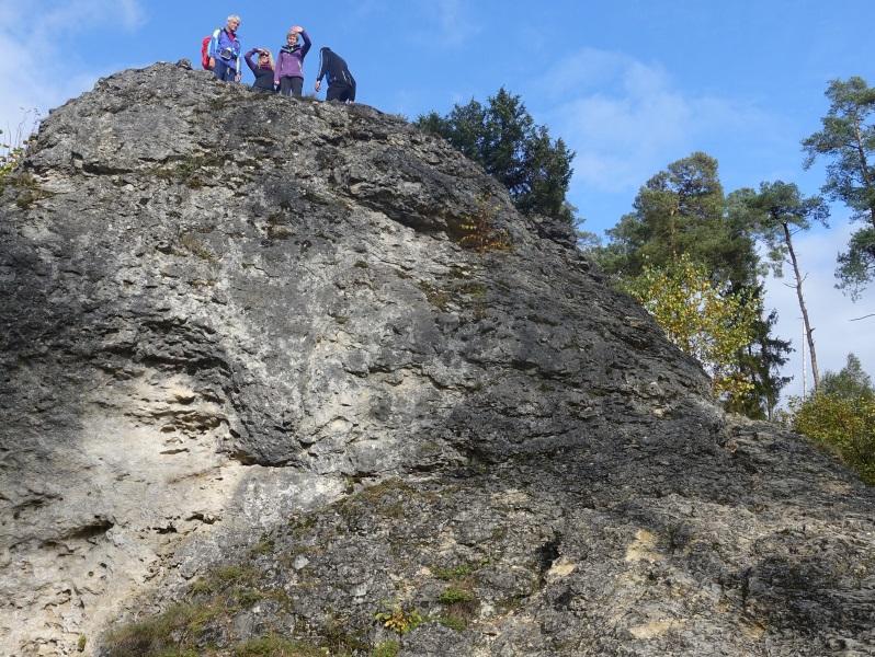 Vier Kletterer auf der Spitze des Felsens winken herunter