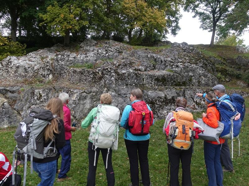 Wandergruppe steht vor Felsen mit vielen Bohrmuschellöchern